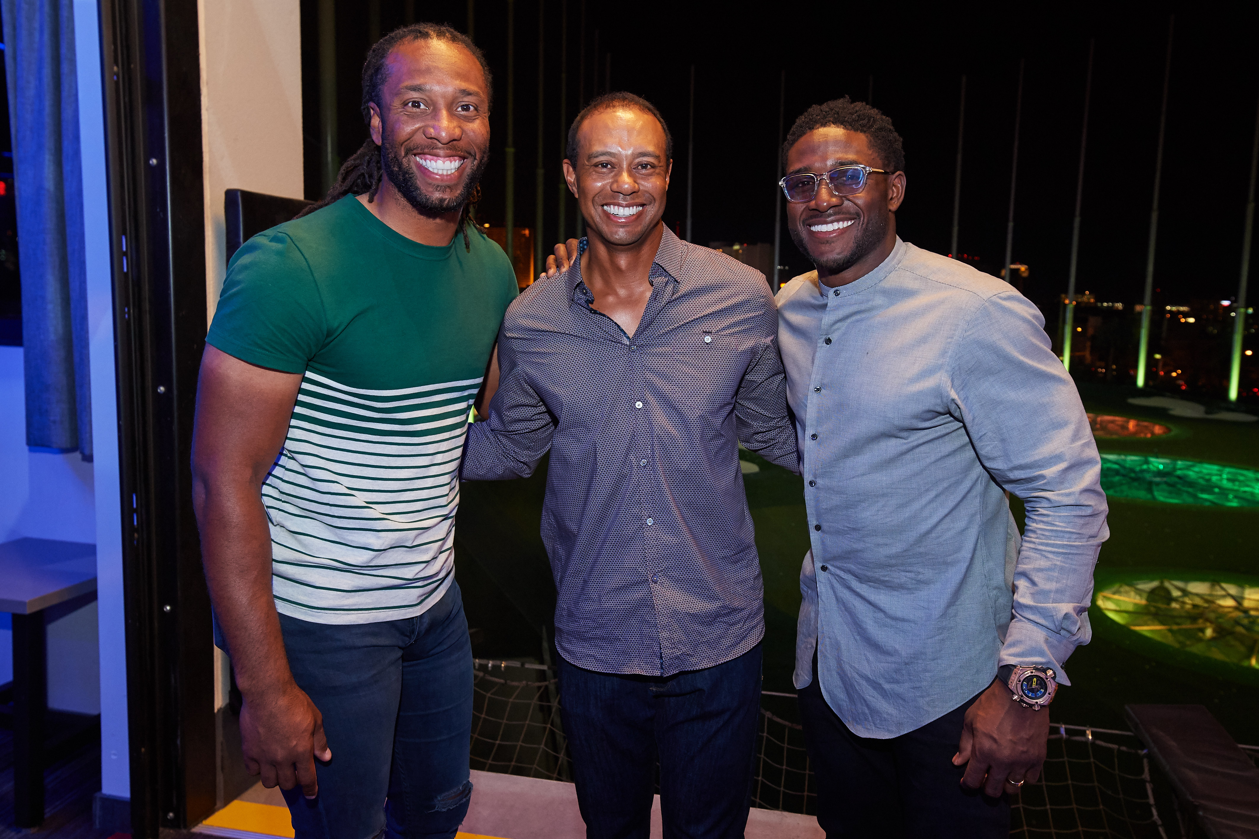 Tiger Woods poses with Larry Fitzgerald and Reggie Bush at Topgolf
